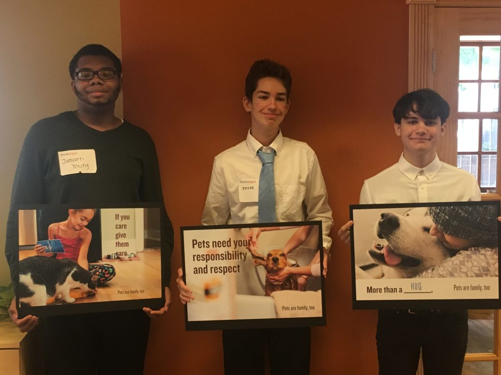 Teen summer interns pose at ThinkArgus with posters they made promoting animal rights