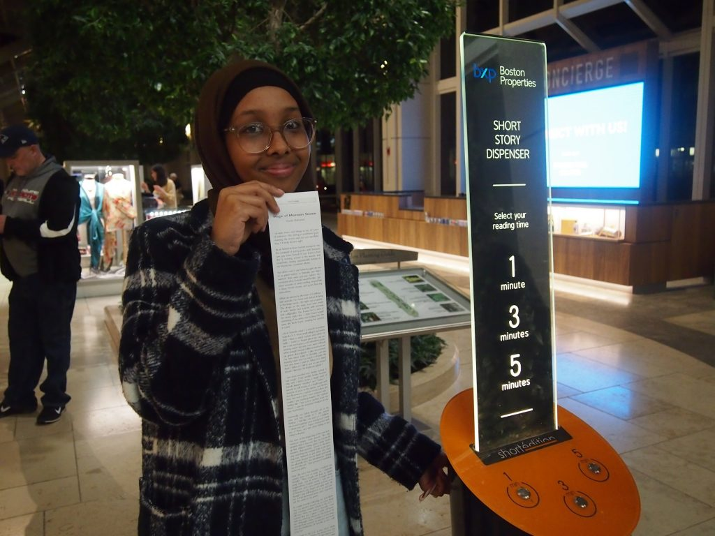 Yasmin shows off her story next to the short story machine in the Prudential Center