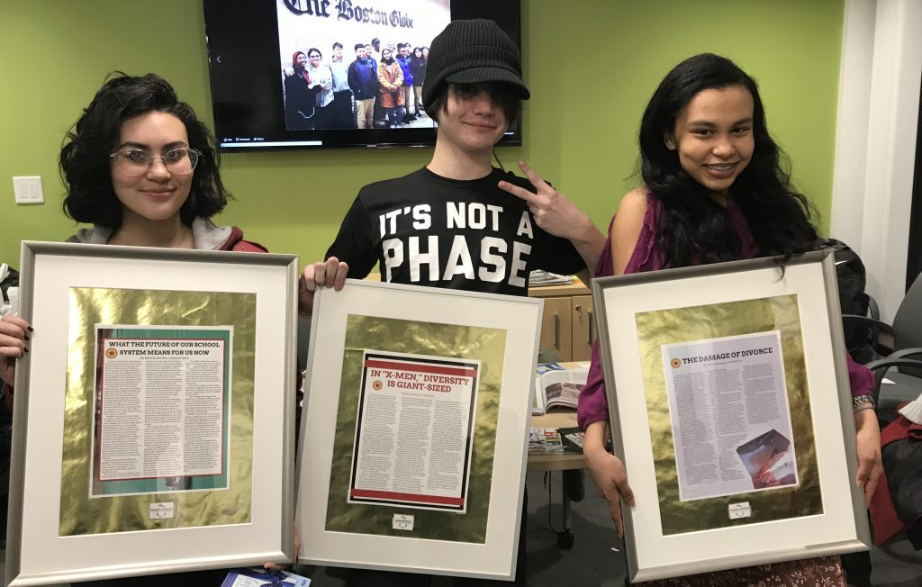 Three students holding rising voices framed awards