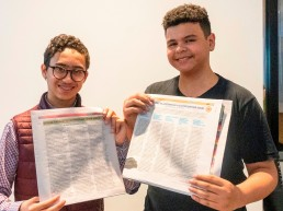 two high school students smiling and holding their articles in Teens in Print