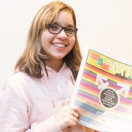 Michaelle Mota - student smiling and holding student newspaper