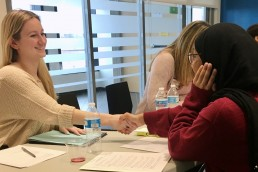 adult professional smiling and shaking hands with a student, preparing for a mock interview
