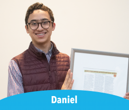 Daniel Smiling student holding framed article