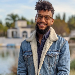 Headshot of Nicholas St. Fleur, wearing a blue denim jacket and smiling with a waterfront and palm trees in the background