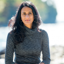 Headshot of Bina Venkataraman, smiling at the camera and wearing a gray dress, with a brightly lit waterfront in the background
