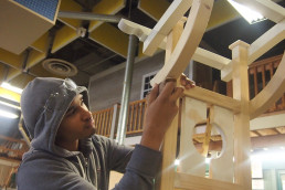 student working on a wooden arch in school